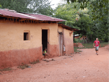 A photo of a rural house in Honduras with a girl sitting by the door and a boy walking in front of her.