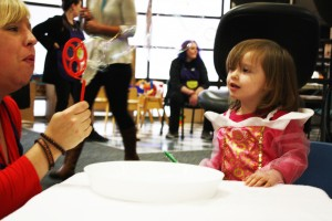 A Spirit of Children volunteer blows bubbles for a little girl in the playroom who is dressed as a Disney princess.