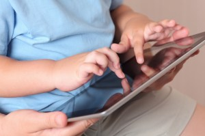 Child and mother using a digital tablet. Close-up.