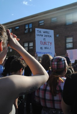 "Protestor holds sign ""The whole damn system is guilty as hell #blacklivesmatter."""
