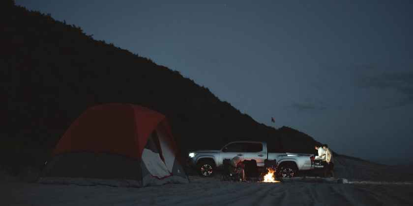 unrecognizable people on beach with camping tent