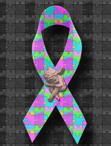 Autism Awarness Cause Ribbon of Colorful Puzzle Pieces with a Cherub Angel Figurine Statue of a Child