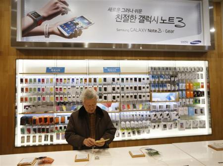 Un hombre prueba un teléfono Galaxy S4 de Samsung en la planta de la firma en Seúl, ene 6 2014
