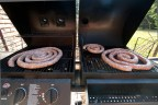 The sausage air dries on an unlit grill