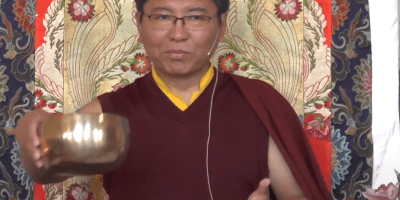 Tsoknyi Rinpoche gestures with metal bowl.