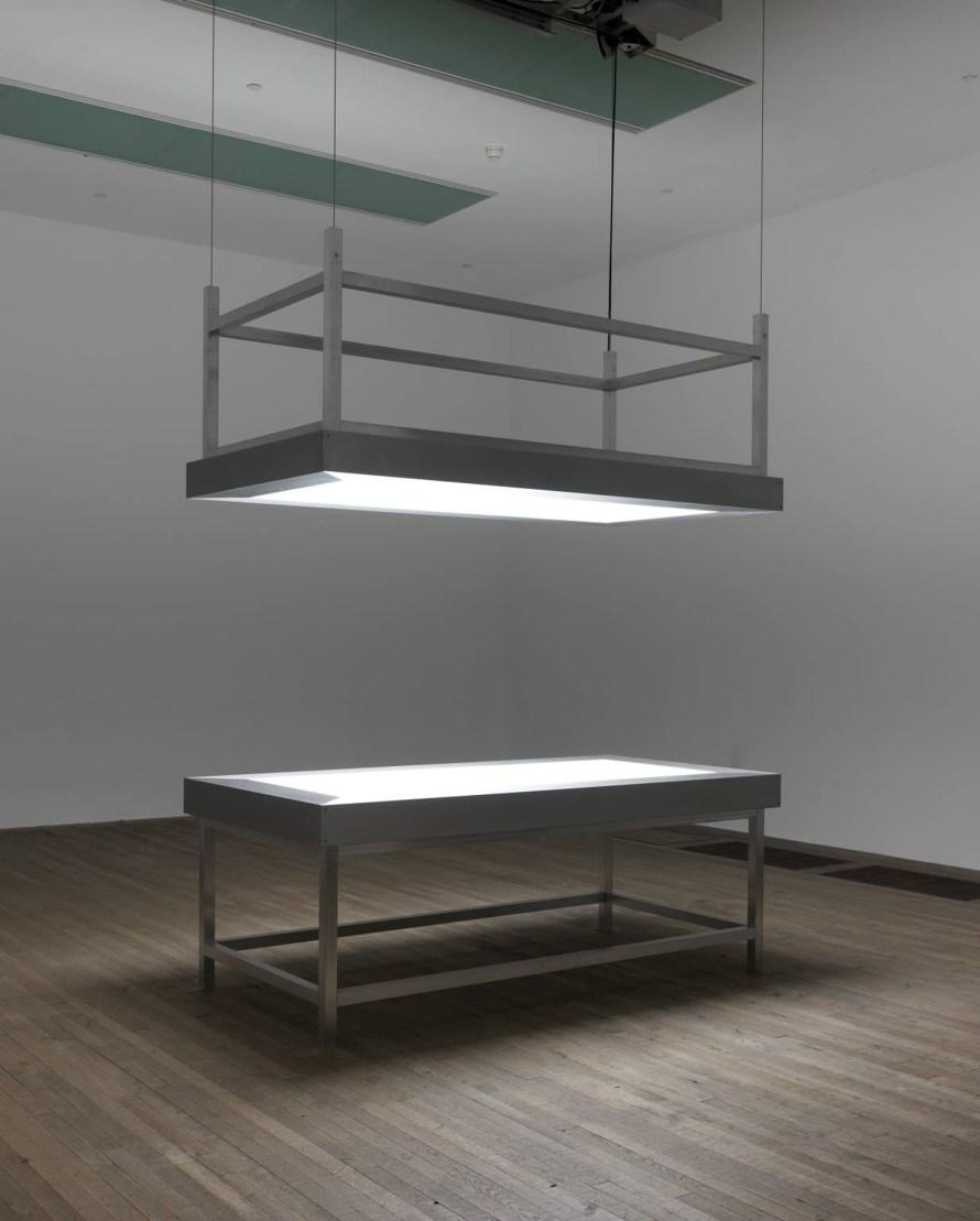 Alfredo Jaar: Lament of the Images, 2002, 2 alumínium asztal, üveg, plexi, neon, motor. © Tate