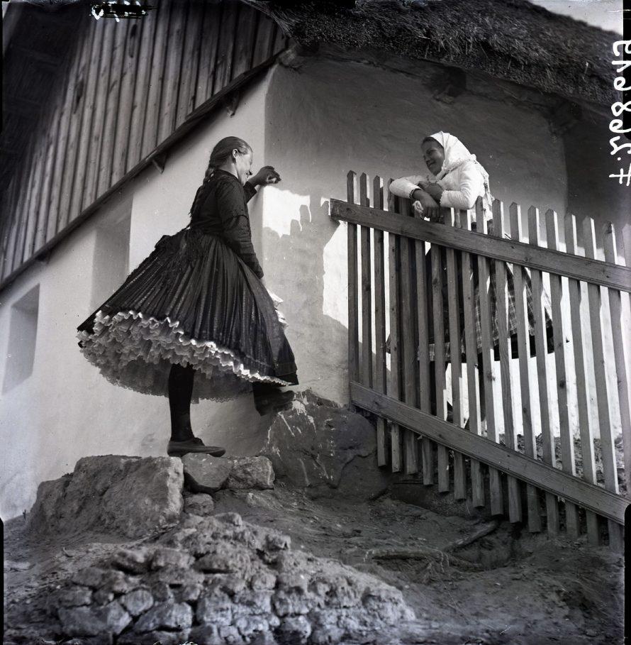 """Fotó: Kerítésnél beszélgető lányok vasárnapi viseletben, a sötét szoknyás lányon """"pigluvanke"""", Csömör, 1940<br> Vadas Ernő felvétele<br> Néprajzi Múzeum, F 268619"""