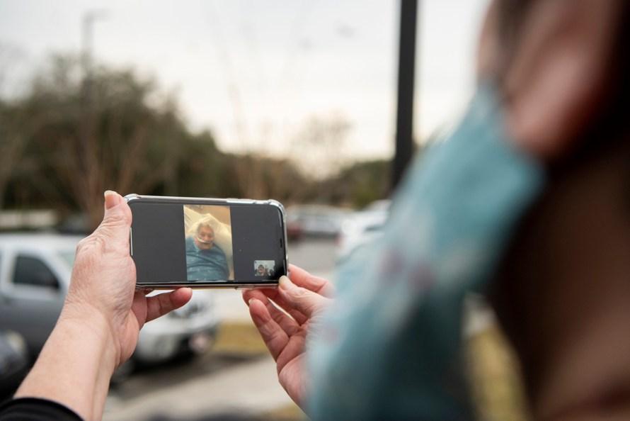 """Lori Daum édesanyjával, Betty Russellel beszél FaceTime-on,  West Marion Kórház, Ocala, Fla., 2021. január 10.  """"Amikor elmentem a kórházból, felnéztem, és nem akartam ott hagyni"""" - mondta Lori. - Tudtam, hogy ez lesz az utolsó alkalom, amikor látom. Fotó: © Tina Russell"""