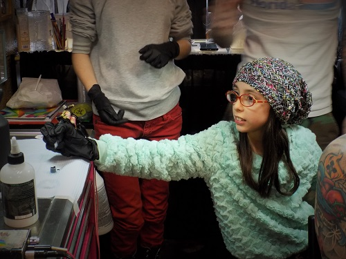 These Kid tattoo artists tattooing Their Dad Will Make You Happy. Mina and Molly, are both under the age of 12 and have been taught to tattoo by their tattoo artist dad, Aaron Is.