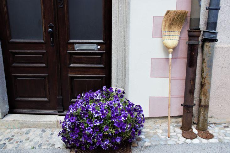 fiori e scopa all'esterno di una casa