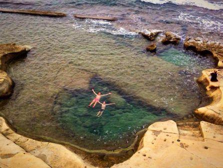 due nuotatori in un anfratto che crea una sorta di piscina naturale a sliema