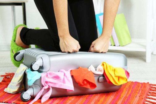 donna che tenta di chiudere una valigia strapiena