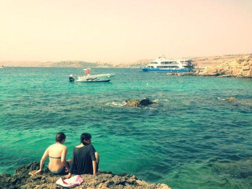 l'acqua blu di comino con due ragazze che osservano il mare nella top 10 di malta