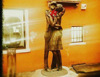 Statua del bacio con fiori rossi