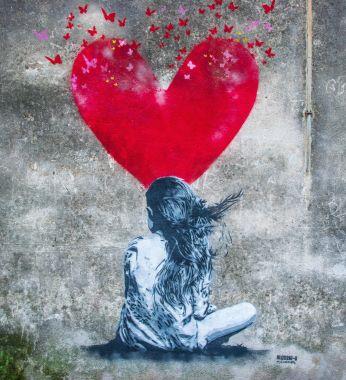 ragazza di schiena con cuore rosso che si dipana in farfalle che volano