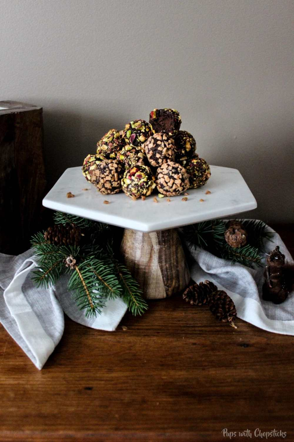 Toffee Orange Chocolate Truffles in a pile on a cake stand with one half eaten
