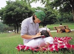 girl sitting on picnic blanket, writing