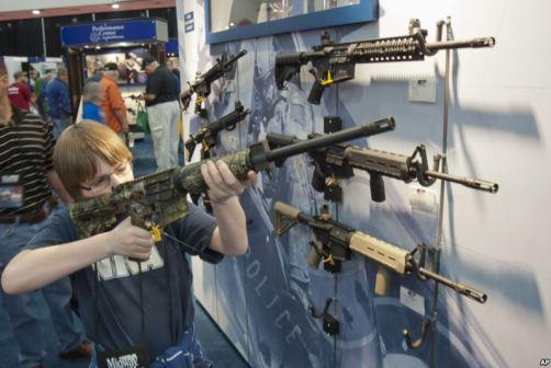 Un garçon essaie une arme pendant la convention annuelle de la National Rifle Association, à Houston, en 2013. Photo Associated Press