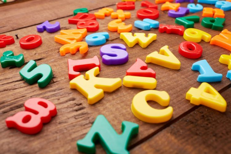 Coloured alphabet magnets scattered on a wooden tabletop