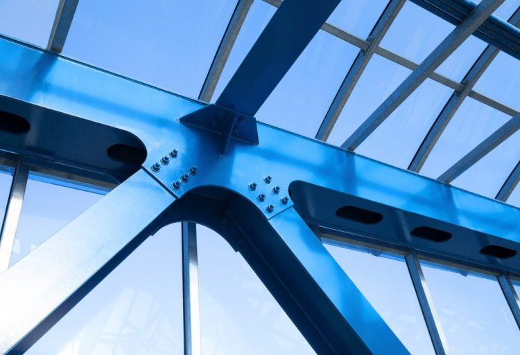 Steel beams silhouetted against blue sky, symbolising structural editing.