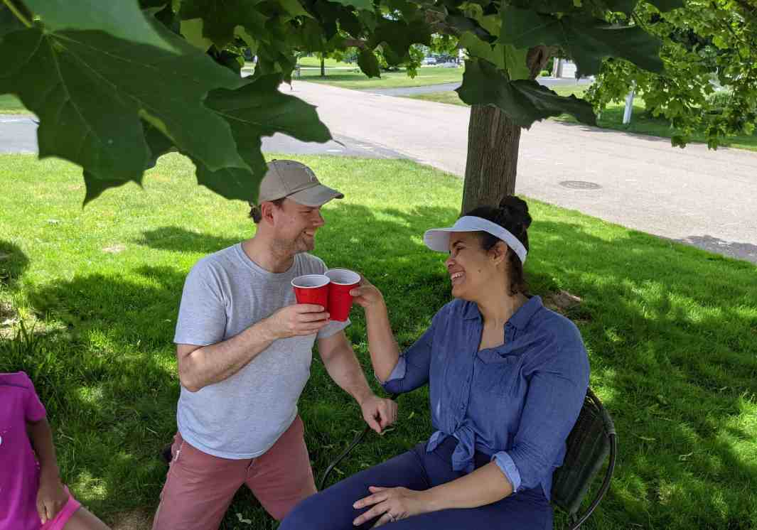 man and woman under a tree toasting