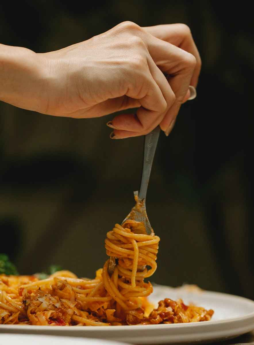 crop woman rolling spaghetti on fork during dinner in restaurant