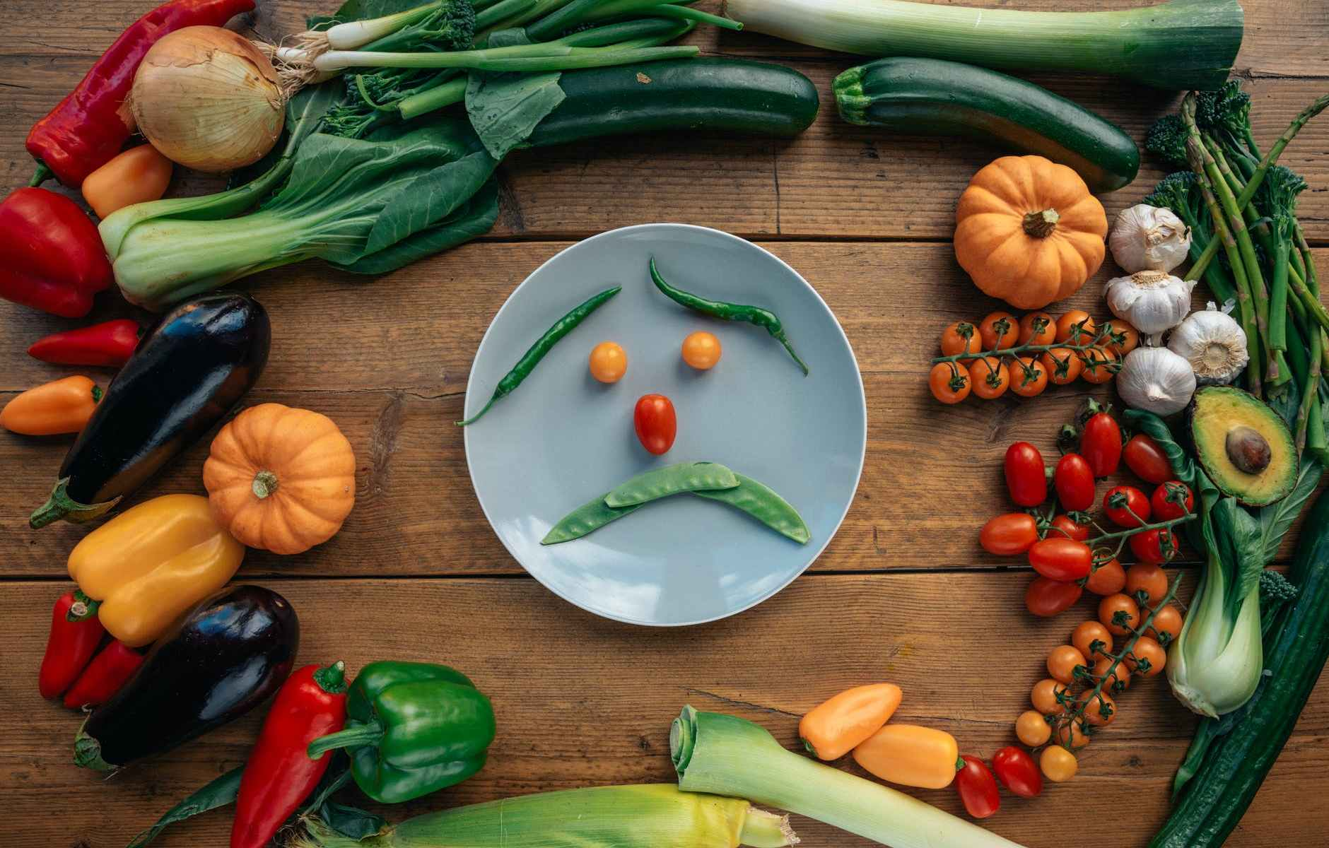 green chili pepper and orange tomatoes on white ceramic plate