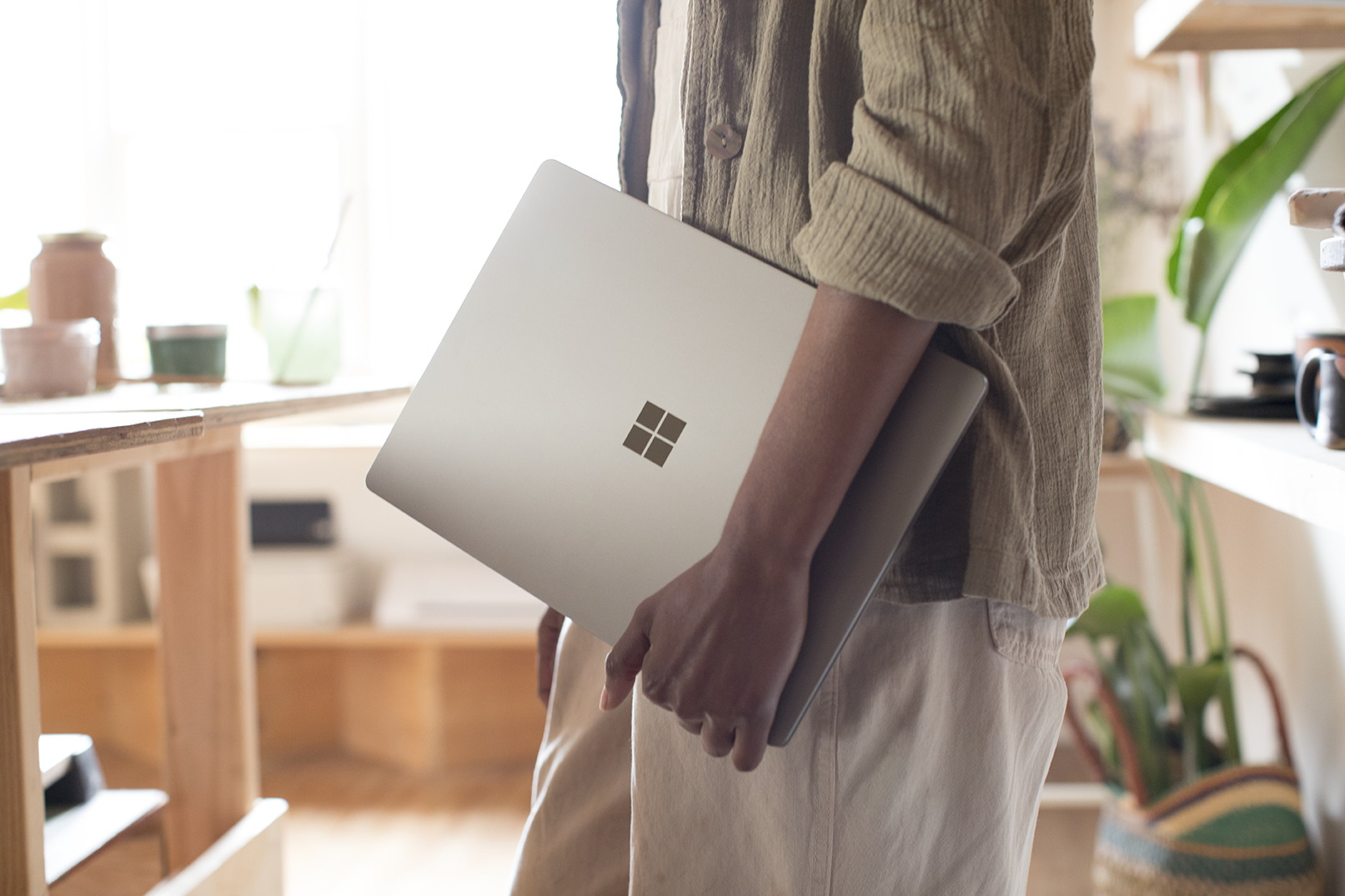 Person holding a Surface Laptop with left arm. Source Microsoft.