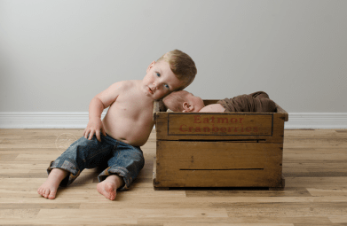 newborn-photos-ottawa-asher-wood-crate-brown-quilt-blanket-sleeping-baby-older-brother-hug-jeans-skin-no-shirt