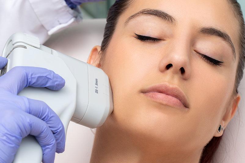 Top view of woman having facial hifu energy treatment.