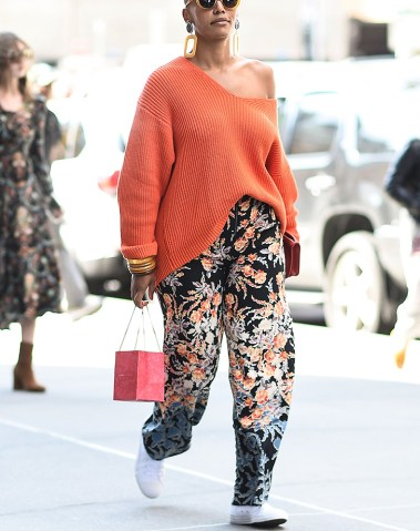 The 10 Best Fashion Tips for Women Over 40   PureWow woman wearing orange off the shoulder sweater and printed pants