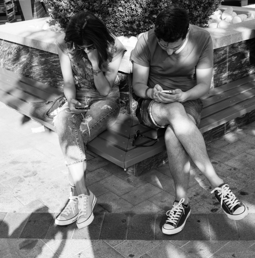 young couple sitting together with phones in hand
