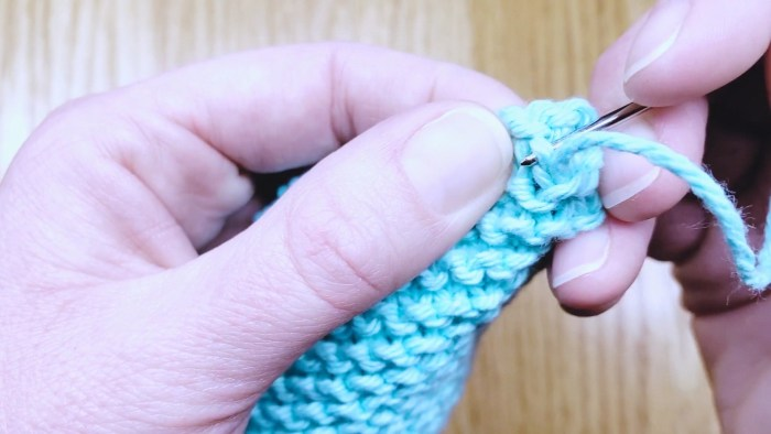 Step 13a: Learn to weave in loose ends and and tie up excess yarn tails - the bind off edge - a knitting lesson from Liz @PurlsAndPixels.