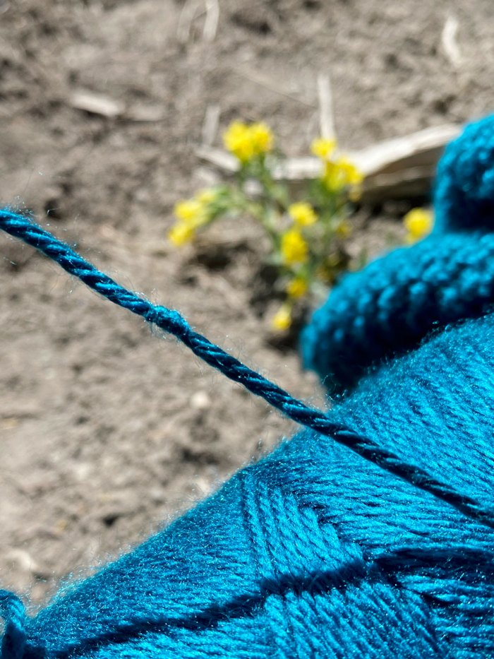Adding a new ball of yarn to your knitting project by making a magic knot creates a tiny, nearly invisible knot anchoring the strands together.