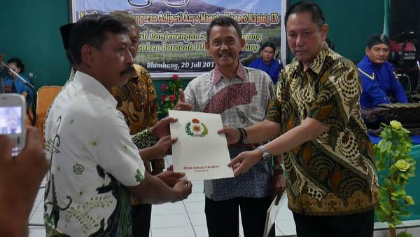 Sri Paduka Mangkunegoro IX menyerahkan surat pelepasan tanah kepada petani penggarap