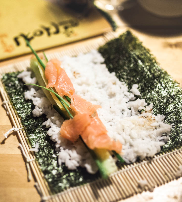An open sushi roll with salmon, cucumber and chives