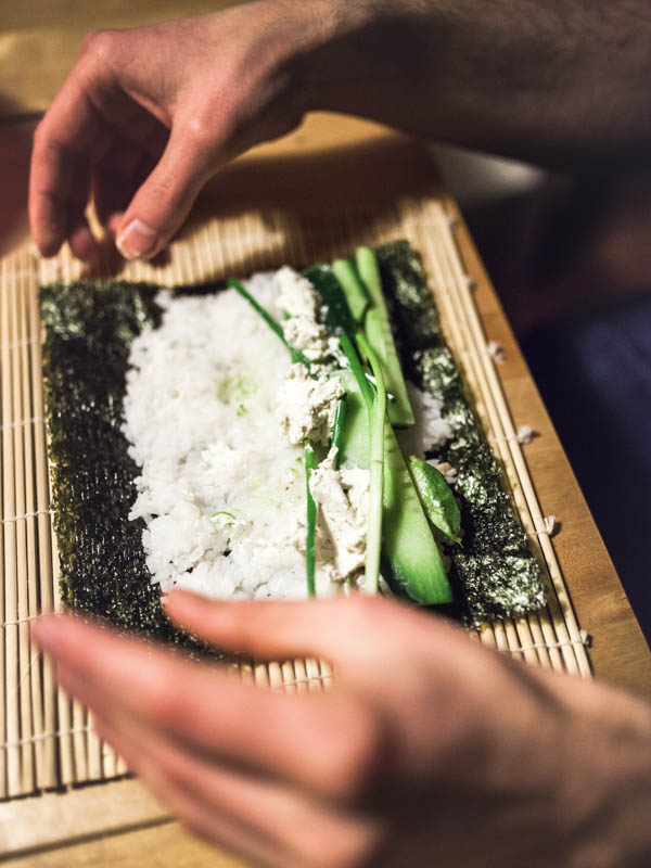Sushi in progress with chives and cucumbber