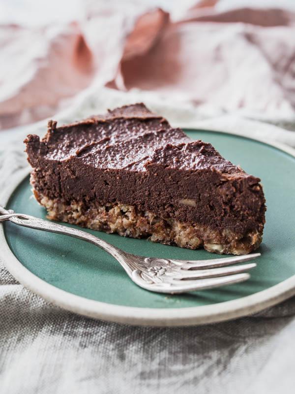 Ein Stück Schokoladenkuchen auf einem grünen Teller. Das Tageslicht kommt von links und schräg hinten.