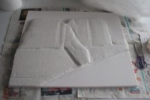 Modroc wetted and placed on top of the cardboard layers, once it's dried it can then be painted.