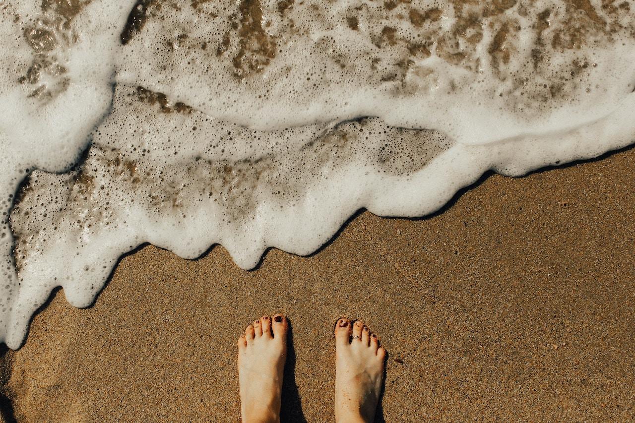 Reflexology - feet on sand with sea