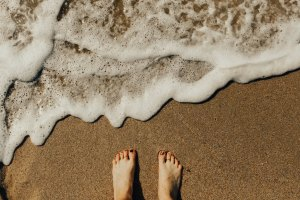 Reflexology - feet on sand with sea