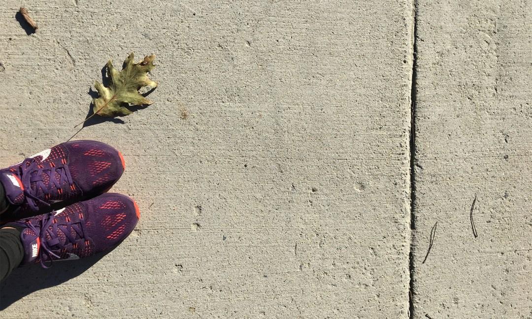 purple sneakers on pavement