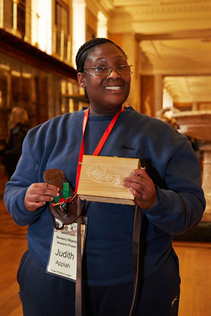 Judith with her sensory label, a wooden lasercut box with replica Ghanaian Slipper.