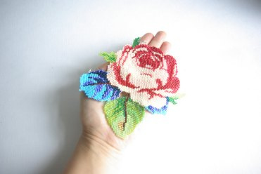 Photo of an hand seen from above holding a giant rose beaded necklace.