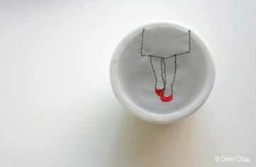 Still life photo of a porcelain cup seen from above with an illustration of two woman legs wearing red shoes.