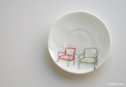 Still life photo of a porcelain plate seen from above with an illustration of two chairs.