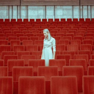 Photo portrait of a woman with a white dress inside a room full of red armchairs.