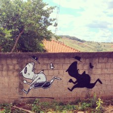 Photo of a wall decorated with a black and shite illustration of a man running.