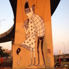Photo of a bridge pole decorated with a giant illustration of a couple kissing.