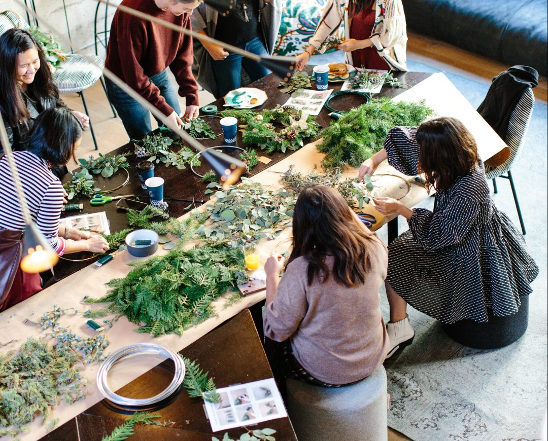 Photo of people crafting wreaths out of lush branches and natural objects.